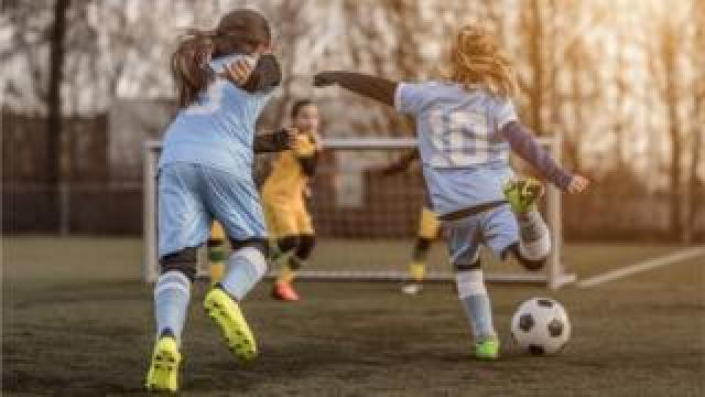 Young girls playing football