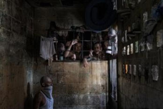 Inmates watch out of an overcrowded cell, while a man wears a bandana over his face due to the putrid smell. Quezaltepeque Criminal Center, El Salvador. November 9, 2018.