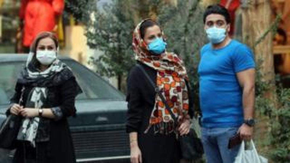 People wearing face masks stand on a street in Tehran, Iran (6 October 2020)