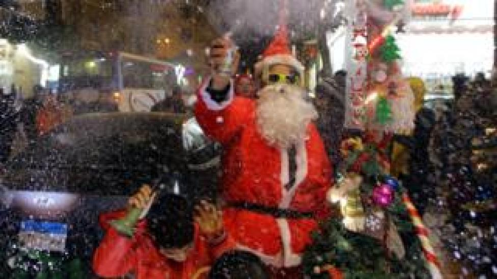"A man wearing a Santa Claus costume selling Santa Claus dolls as part of New Year""s Eve celebrations at a market in Cairo, Egypt, 31 December 2017"