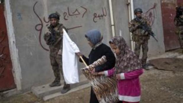 درحالی که سربازان ارتش در جستجوی نفرات داعش هستند غیرنظامیان با پرچم سفید عبور می کنند