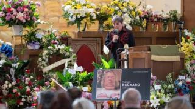 A woman speaks during the funeral of Margie Reckard