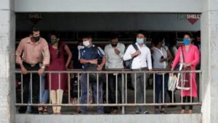 Passengers wait for a bus in Colombo, Sri Lanka