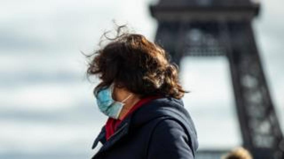 A tourist wears a face mark in front of the Eiffel Tower in Paris