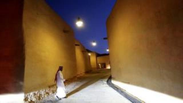 A Saudi man walks past renovated buildings at the historic city of Diriyah