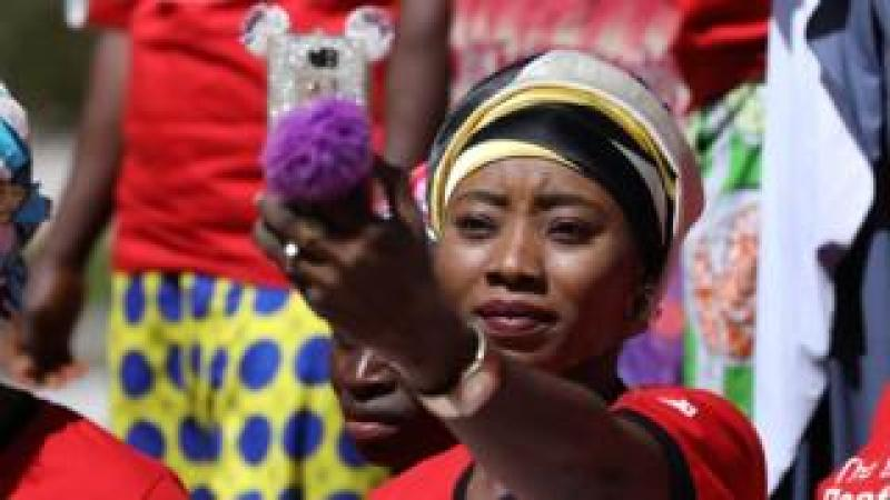 A woman at a rally in Abuja taking a selfie in Abuja, Nigeria - Tuesday 5 December 2017