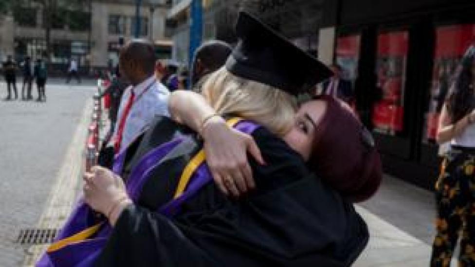 Two graduates embrace
