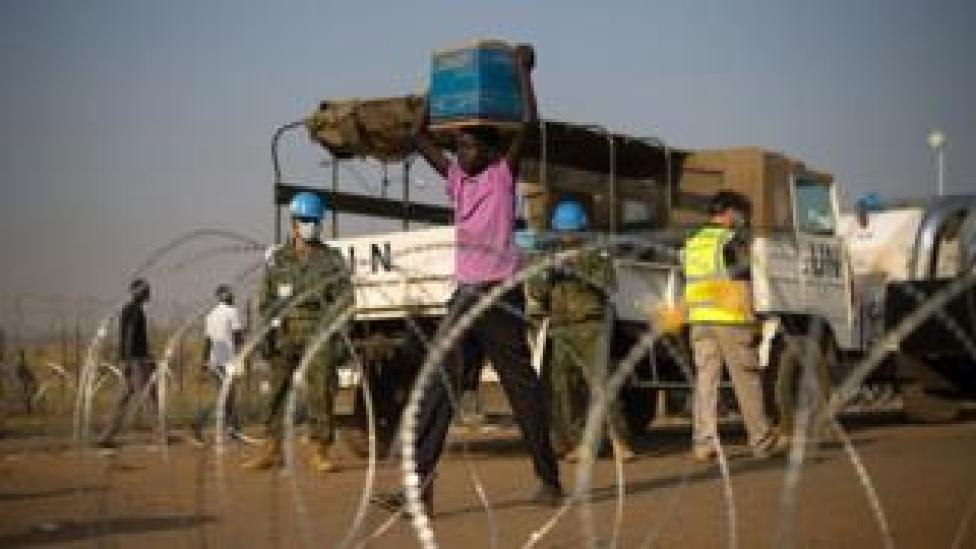 South Sudanese carries aid from a UN truck (archive photo)