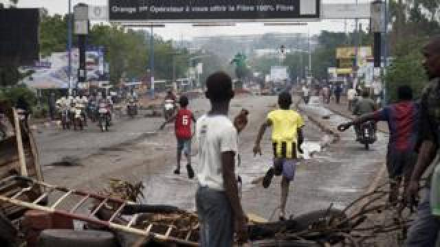 People run away at the arrival of the riot police as protesters set barricades in Bamako