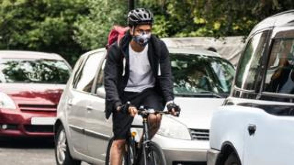 A cyclist next to traffic