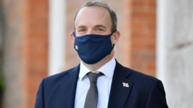 Foreign Secretary Dominic Raab wearing a face mask waits for the French and German foreign ministers to arrive for an E3 Ministers meeting at Chevening House in Sevenoaks, Kent
