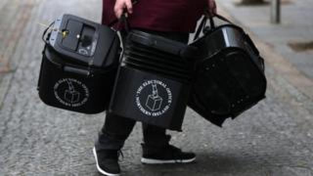 A man carrying ballot boxes