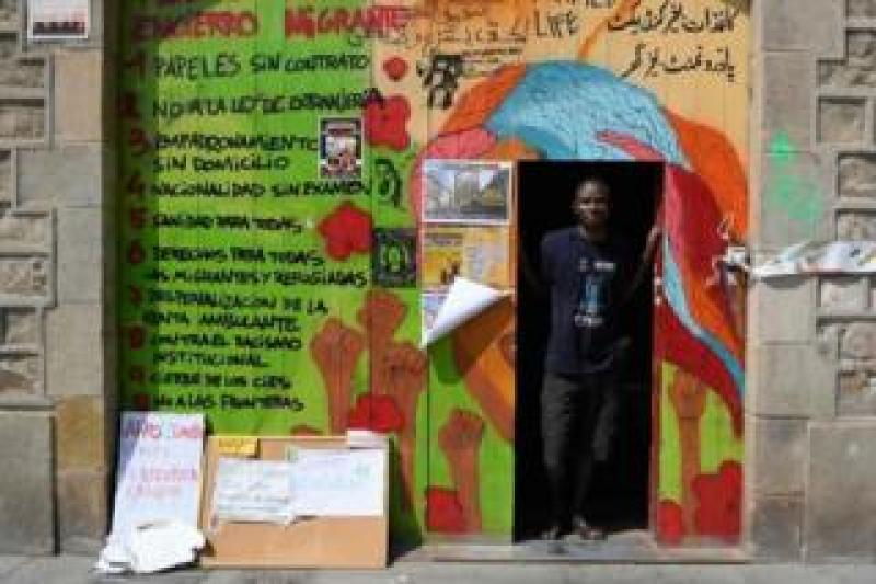 Ugandan Francis Kashamba poses at the frontdoor of the abandoned school of La Massana, in the center of Barcelona, on July 3, 2018, occupied since mid-April by dozens of migrants. Once far from the strife that pushed them to come to Europe, what has awaited thousands of illegal migrants in Spain is a form of agonising purgatory, according to the migrants occupying the Massana School