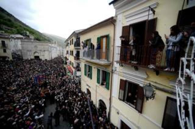 People watch from a balcony as a statue of Saint Domenico covered with live snakes is carried by faithfuls during an annual procession in the streets of Cocullo