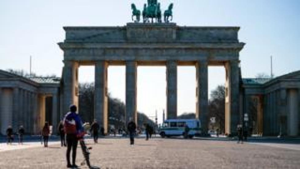 A police car drives in front of the Pariser Platz square in front of the Brandenburg Gate in Berlin