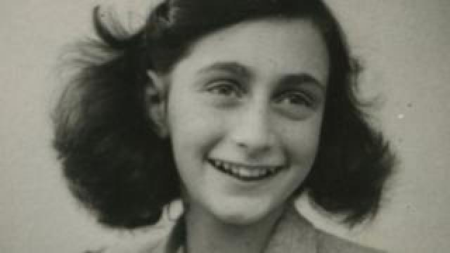 Anne Frank smiles in a black and white photo