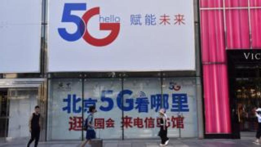 People walk past a China Telecom 5G advertisement on July 25, 2019 in Beijing, China