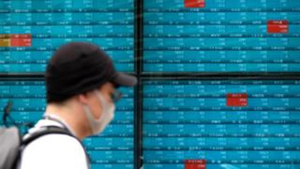 Man walks past market boards in Tokyo.
