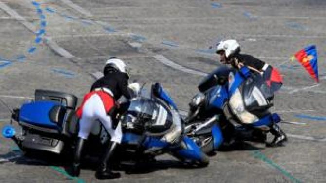 Gendarmes pick up their bikes after colliding