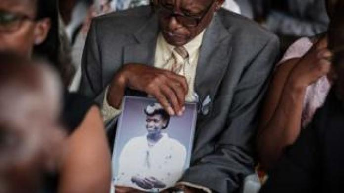Vianney Rusanganwa, 61, holds a portrait of his late wife Liberatha Mukangira who died aged 31, during the mass funeral to bury 81 coffins containing newly discoverd remains of 84,437 victims of the 1994 genocide in the mass grave at the Nyanza Genocide Memorial, suburb of the capital Kigali, on May 4, 2019. - The remains of nearly 85,000 people murdered in Rwanda's genocide were laid to rest on May 4 in a sombre ceremony in Kigali, a quarter of a century after the slaughter.