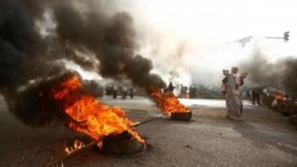 Un manifestant avec des pierres pavées passe devant des pneus en flammes à Khartoum, au Soudan. Photo : 3 juin 2019