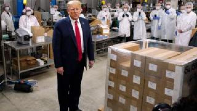 Employees take photos as President Trump speaks during a tour of a US factory.