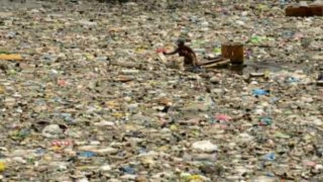 A scavenger wades through garbage in Manila, 2016