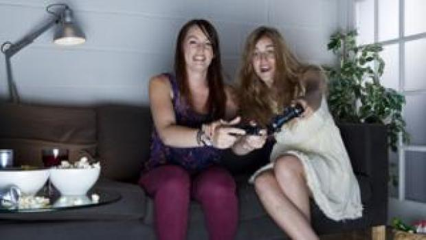 Two young women with cheerful expressions playing video games on a sofa