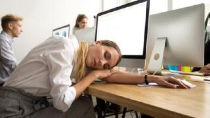 Woman asleep on a desk