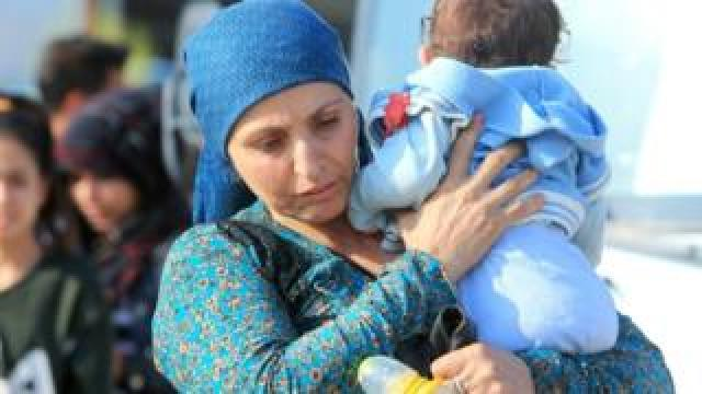 A displaced Syrian woman, who fled violence after the Turkish offensive in Syria, carries her baby