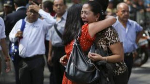 Two women embrace as one cries on the street in Mexico City