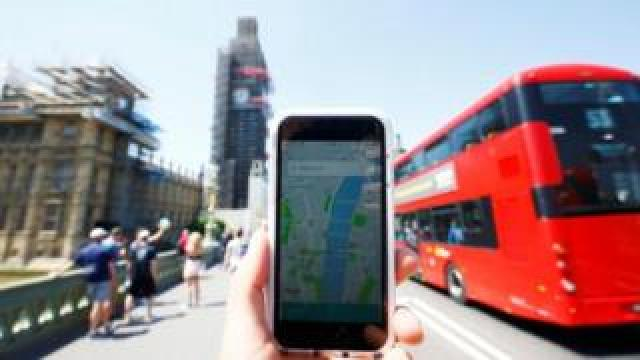 Mobile phone with Uber app in front of Big Ben
