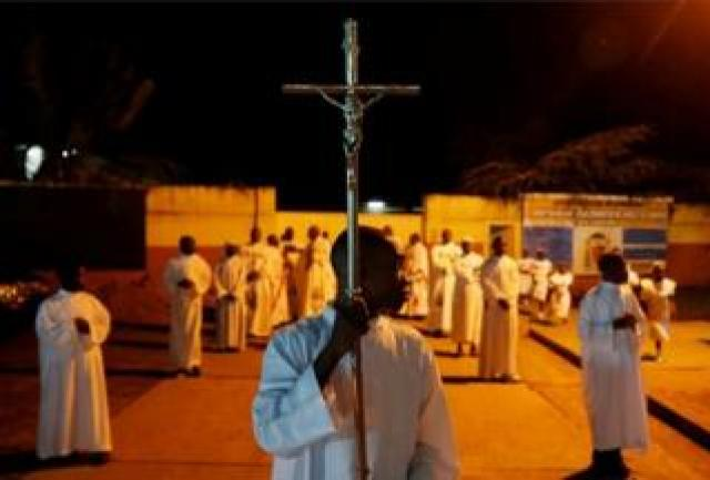 An altar boys holds a cross before a mass at the Notre Dame de Kinshasa cathedral in Kinshasa, the Democratic Republic of Congo