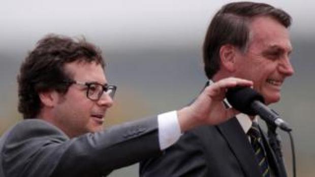 Fabio Wajngarten mutes the microphone for Brazil's President Jair Bolsonaro