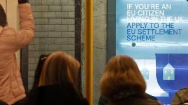 A poster encouraging EU nationals to apply to the government's post-Brexit EU settlement scheme is pictured through a carriage of a London Underground tube train