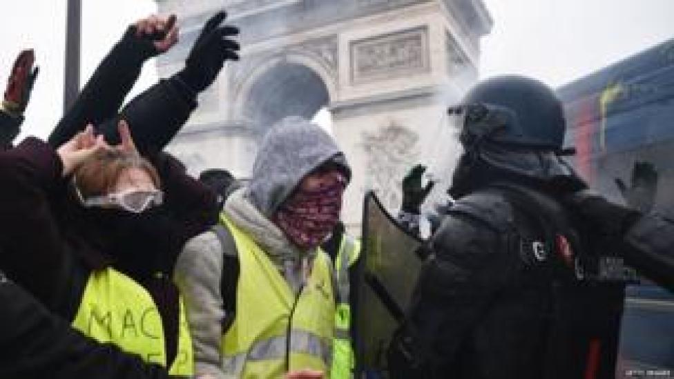 Des manifestants masqués affrontent des policiers près de l'Arc de Triomphe, à Paris (1er décembre)