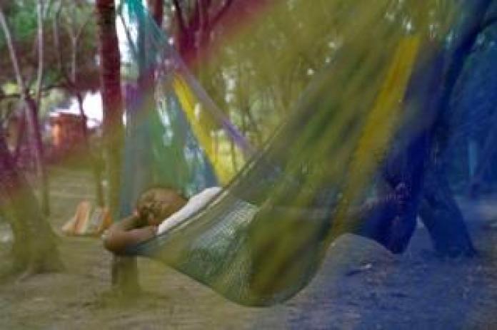 A Mexican asylum-seeking woman sleeps in a hammock
