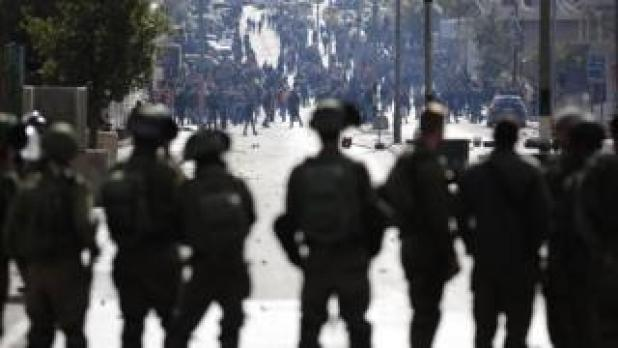 Israeli soldiers watch on as Palestinians gather in Bethlehem on 7 December 2017