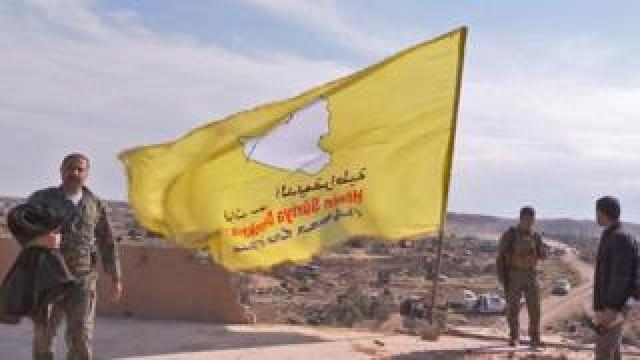 Syrian fighters raise a yellow flag as they celebrate the defeat of IS