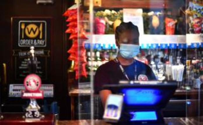 A bar worker uses a till behind a pub bar