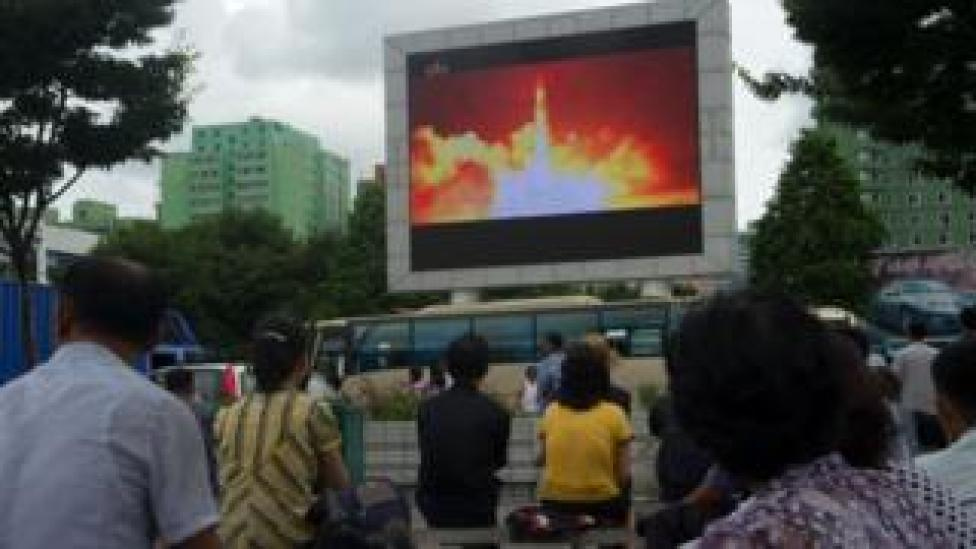 People watch coverage of an ICBM missile test on a screen in a public square in Pyongyang on July 29, 2017.