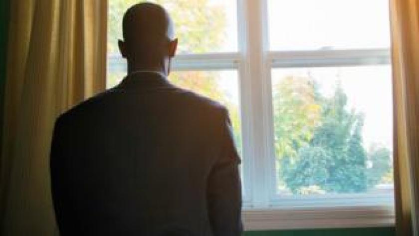 Man staring out of window