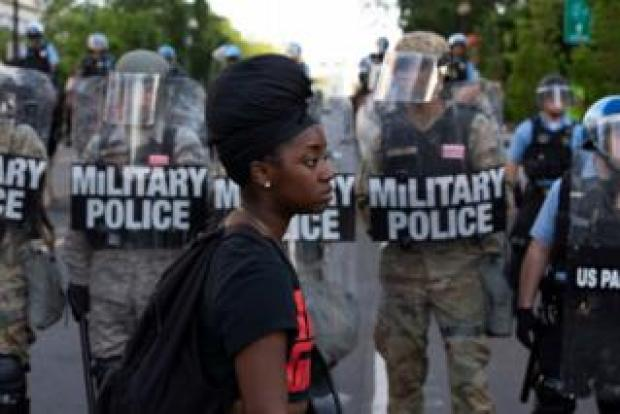 Black woman in front of police in riot gear