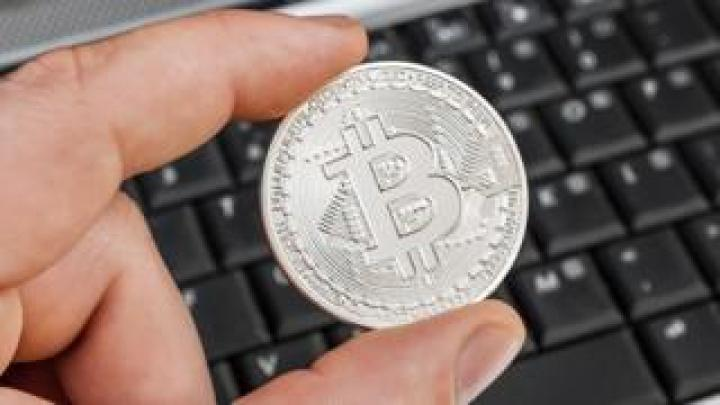 Man's hand holding 'bitcoin' over laptop keyboard