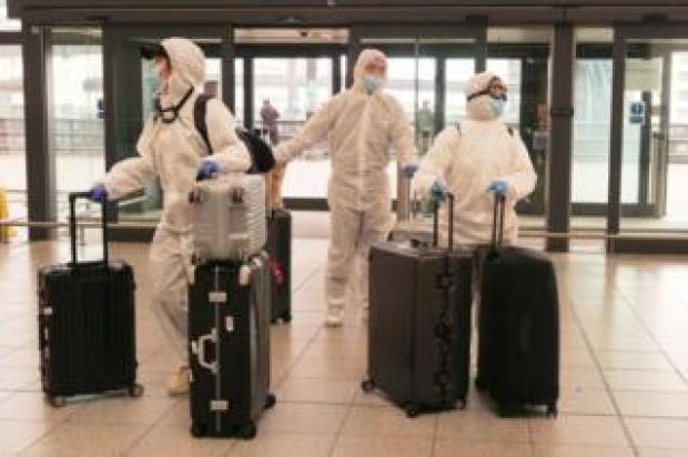 Passengers determined to avoid the coronavirus before leaving the UK arrive at Gatwick Airport departure area.
