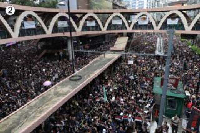 The street can no longer be seen beneath the heaving crowd in this shot of a light rail station, the ring and arches of its architecture visible above them