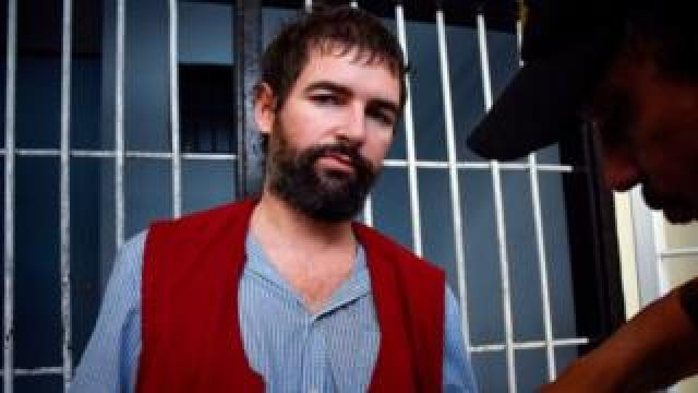 Frenchman Felix Dorfin is escorted back to prison after he was sentenced to death by a court in Mataram