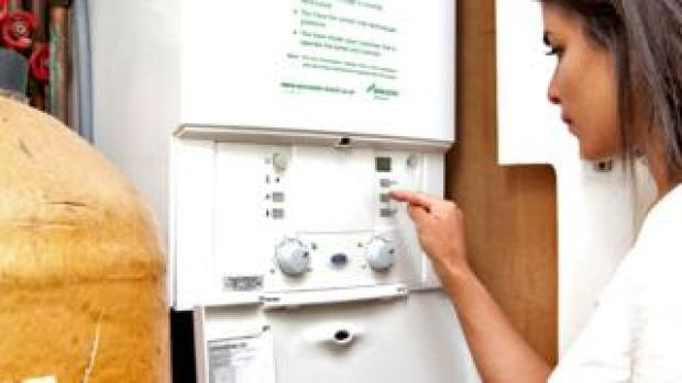 Woman using a gas boiler