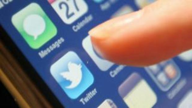 Thumb hovering over Twitter application