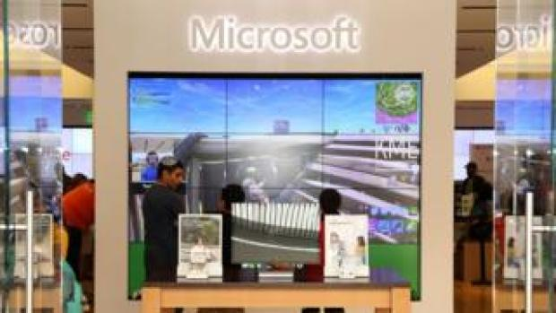 A giant Microsoft logo above a wall screen showing Fortnite being played by a streamer - inside a Microsoft branded store